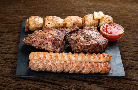 Stone board with different tasty cooked meat on wood background. Veal kebab, lyulya, potatoes. Фото со стока