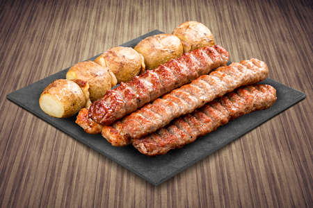 A selection of various barbecued gourmet meats on a black board with a rustic timber background.Various meat kebab with baked potatoes