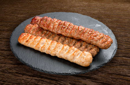 Stone board with different tasty cooked meat on wood background. Various meat kebab Фото со стока