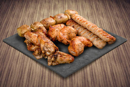 A selection of various barbecued gourmet meats on a black board with a rustic timber background. Assorted meat