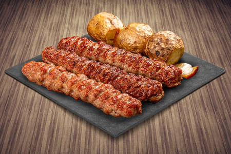 A selection of various barbecued gourmet meats on a black board with a rustic timber background. Chicken kebab with baked potatoes