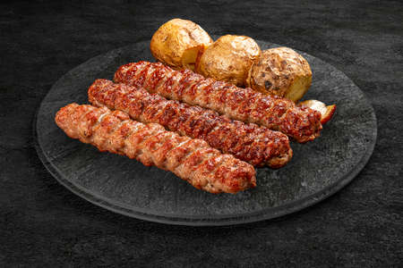 A selection of grilled gourmet meats on a rustic stone board. Various kebab with baked potatoes Фото со стока