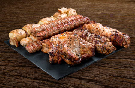 Stone board with different tasty cooked meat on wood background. Pork neck, potatoes, kebab