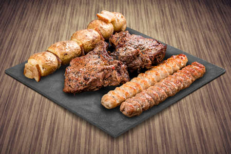 A selection of various barbecued gourmet meats on a black board with a rustic timber background. Pork neck, potatoes, kebab.