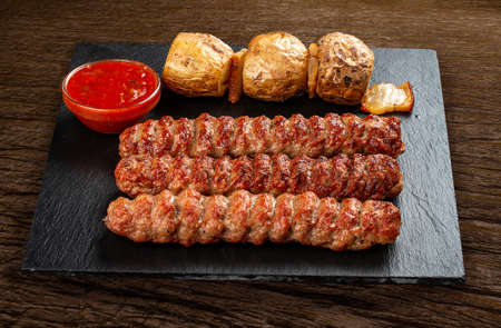 Stone board with different tasty cooked meat on wood background. Chicken kebab with baked potatoes