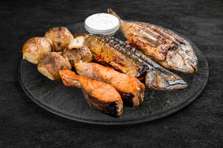 A selection of grilled gourmet meats on a rustic stone board. Assorted meat and fish