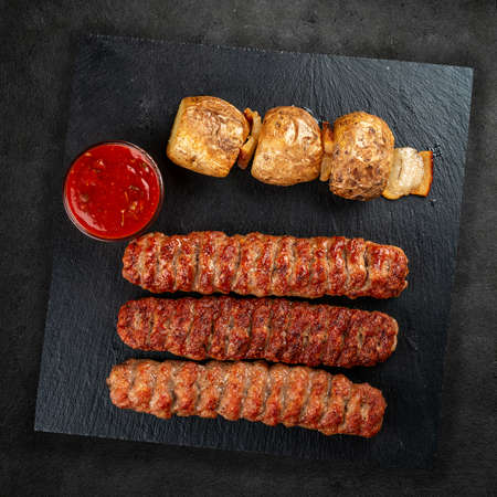 Assorted delicious grilled meat on a stone board. Top view