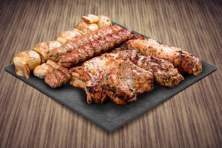 A selection of various barbecued gourmet meats on a black board with a rustic timber background. Pork neck, potatoes, kebab