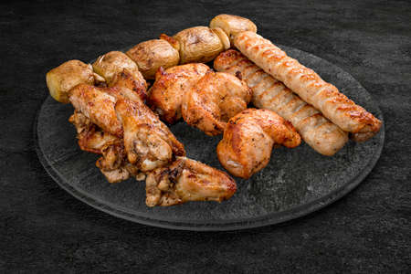A selection of grilled gourmet meats on a rustic stone board. Assorted meat