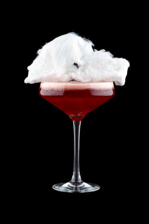 Cherry cocktail with cotton candy on a dark background. Isolated