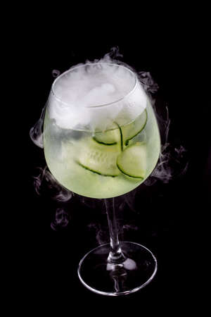 Martini cocktail, tonic and cucumber on a dark background. Isolated Фото со стока