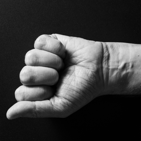 Black & white image of man's wrinkled hand, with clenched fist as if holding something, wrist with visible strong vein lines, isolated against a black background with dramatic sidelight