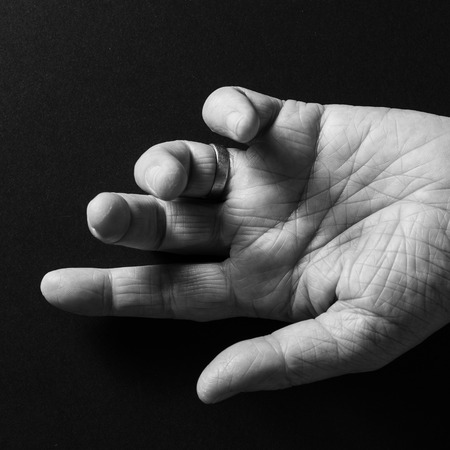 Black & white image of man's wrinkled left hand, open palm up and pointing to left, isolated against a black background with dramatic sidelight