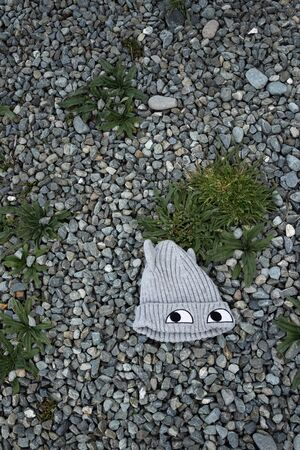 Child's knitted woollen grey beanie hat with eyes, lying abandoned or dropped on ground and surrounded by gravel & weeds, viewed from above