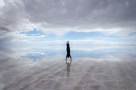 Happy, joyful woman doing handstand on salt flats, Salar de Uyuni, Bolivia, with dark storm clouds, bright blue sky and infinite horizon reflected in pools of water Stock Photo