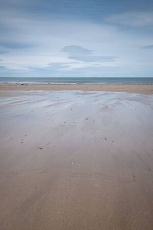 Shimmering, silvery, wet, sandy beach with cloudy, blue sky reflected in water pools below, St Andrews, Fife, Scotland