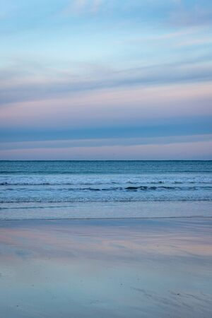 View to distant horizon over rolling waves with bright, vibrantly coloured sunset above reflected in shimmering, wet, sandy beach, Scotland