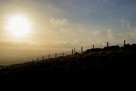 Silhouette of stone boundary wall & wire fence against dramatic, cloudy, golden sunset & bright blue sky, Lomond Hills, Fife, Scotland