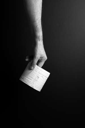 black & white image of single male hand carrying toilet roll by finger tips, set against dramatic dark background and lighting