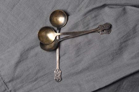 Ancient metal tablespoons on gray fabric Archivio Fotografico