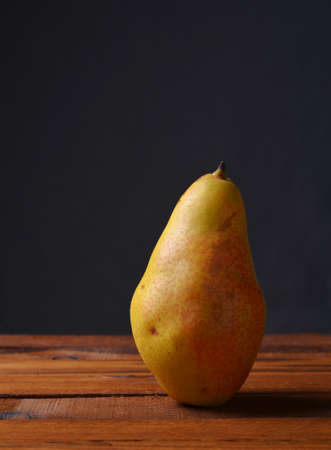 Yellow pear on boards gray background