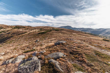 red grass: Hill with red grass and rocks with deep blue sky Stock Photo