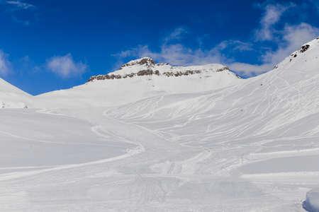 Montañas nevadas con trazadores de esquí Foto de archivo
