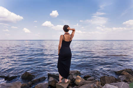 stoned: The Girl stand on stoned river bank on sky background