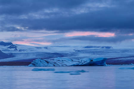Icebergs floating in Fjallsarlon glacier lake at sunset. South Iceland.Close to Jokulsarlon lagoon./ Icebergs floating in Fjallsarlon glacier lake at sunset. Stock Photo - 64671917