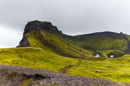 Big tall hill with are climbing up tourists in Iceland Stock Photo