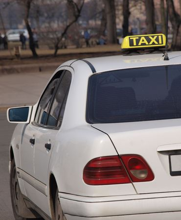 photo story:         Color photo of a white car with a taxi sign on the roof. The City story.