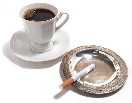 Color photo of a cup of coffee and a cigarette in an ashtray          photo