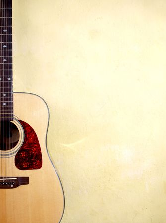 Color photo of an acoustic guitar near wall photo