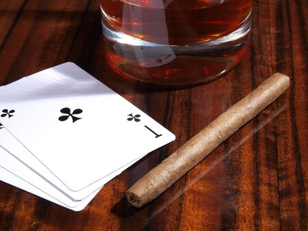 Color photo of cigars, playing cards and cups on a wooden table    photo