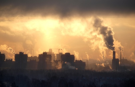 haze: Color photograph of industrial buildings at sunset sky