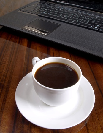 Color photo of a workplace with a laptop and a cup of coffee          Stock Photo - 9501436