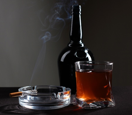 cigarette: Color photo of a glass of whiskey and cigarettes