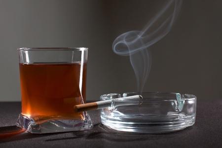 veneno frasco: Fotograf�a en color de un vaso de whisky y cigarrillos Foto de archivo