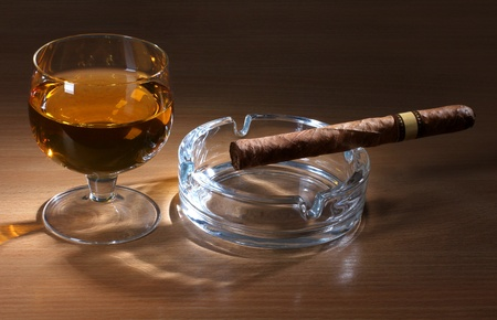 Color photo of a glass of whiskey and a big cigar photo