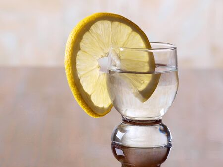 Color photo of a glass cup with tequila and lemon      photo