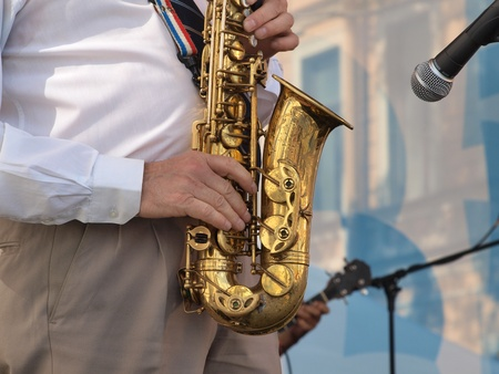 Color photo of a man with a saxophone on stage         photo