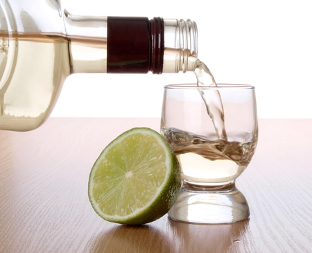 Color photo of a glass of tequila and lemon