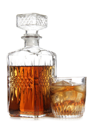 BARWARE: Glass decanter of whiskey on white background
