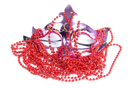 Theatrical mask and red beads on a white background photo