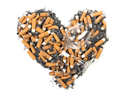 Broken heart and cigarette butt on a white background photo