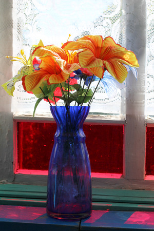 flower: Bouquet of flowers in a glass vase against a window