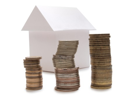 model home: Paper model home and coins on white background