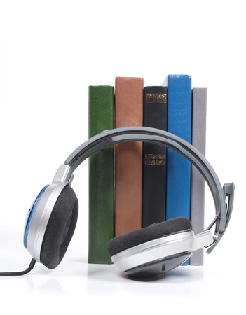 audible: Stack of books and headphones on white background Stock Photo