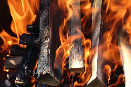 oven range: Charred wood and bright flames on dark background Stock Photo