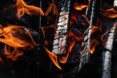 clod: Charred wood and bright flames on dark background Stock Photo